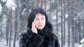 Brunette girl in a black coat talking on the phone and smiling against the background of a winter park or forest during stock video footage