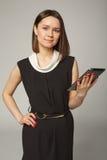 Brunette girl in black dress holding ipad over. Grey stock image