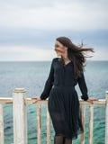 Brunette girl in a black dress posing on the pier stock image