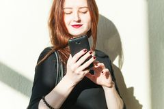 Brunette girl black dress uses smartphone in office royalty free stock image