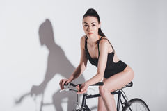 Brunette girl in black fashionable bodysuit sitting on bicycle and looking away on grey Stock Images