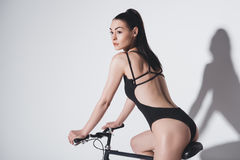 Brunette girl in black fashionable swimsuit sitting on bicycle and looking away on grey Stock Photos