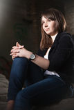 Brunette girl in black jacket sitting in dark room Stock Photography