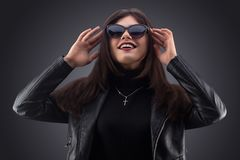 Brunette girl in a black leather jacket . Beautiful model on a gray background. Royalty Free Stock Photography