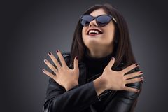 Brunette girl in a black leather jacket . Beautiful model on a gray background. Royalty Free Stock Image