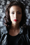 Brunette girl  in a black leather jacket. Portrait of a fashionable brunette girl  in a black leather jacket over wallpaper background. Rock star style. Daylight Royalty Free Stock Images