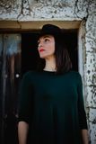 Brunette girl in black with a stylish hat and a old wooden door Stock Images