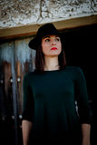 Brunette girl in black with a stylish hat and a old wooden door Stock Photography