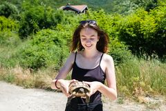 Brunette girl in a black t-shirt holds a land turtle in her hands and look on it. stock photography