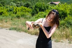 Brunette girl in a black t-shirt holds a land turtle in her hands and look on it in the village stock photo