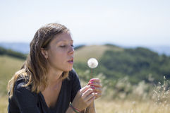 Brunette girl blowing a dandelion in the field Royalty Free Stock Photo
