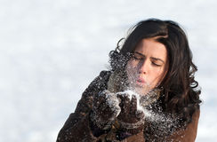 Brunette girl blowing on the snowflakes Stock Image