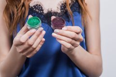 Brunette girl in blue dress is holding open a glitter green and brown, cosmetics, eyeshadow, shiny, manicure, fingers, closeup royalty free stock image