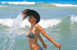 Brunette girl in blue sea Stock Images