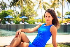 Brunette girl in blue sits on stone barrier against pool Stock Images
