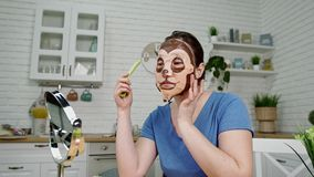 Girl put on cosmetic mask eats celery at mirror in kitchen. Brunette girl in blue t-shirt put on cosmetic mask and eats celery sitting at table in front of round stock video footage