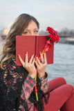 Brunette girl with a book by the river bank Royalty Free Stock Photography