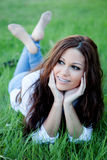 Brunette girl with brackets lying on the grass Royalty Free Stock Images