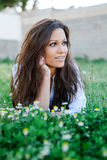 Brunette girl with brackets lying on the grass with many flowers Royalty Free Stock Images