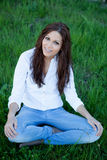 Brunette girl with brackets sitting on the grass Stock Image
