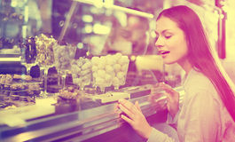 Brunette girl buying dark and white chocolate with fillings Stock Photo