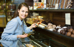 Brunette girl buying dark and white chocolate with fillings Royalty Free Stock Images