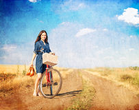 Brunette girl with bycicle. On countryside road Stock Photo