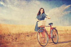 Brunette girl with bycicle. Brunette girl  with bycicle on countryside road Royalty Free Stock Image