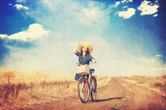 Brunette girl with bycicle. On countryside road Stock Images