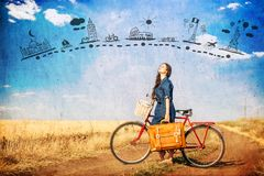 Brunette girl with bycicle and suitcase on country side road. Brunette girl with bycicle and suitcase on country side road and abstract travel map in air stock photos