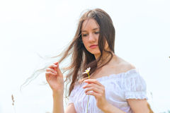 Brunette girl with a camomile in a hand Stock Photo