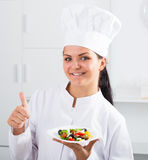Brunette girl chef  and plate with salad Stock Photo