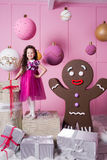 Brunette girl child 5 years old in a pink dress. in holiday rose quartz room with gifts. Stock Images