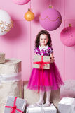 Brunette girl child 5 years old in a pink dress. in holiday rose quartz room with gifts. Royalty Free Stock Photography