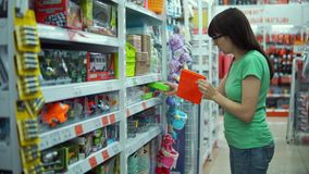 Young woman chooses small plastic basket in store. stock footage