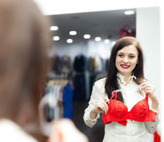 Brunette  girl choosing  bra at  store Royalty Free Stock Image
