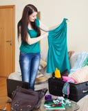Brunette girl choosing dress for vacation Stock Photos