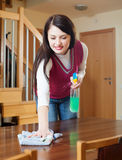 Brunette girl cleaning table with cleanser Royalty Free Stock Photo