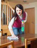 Brunette girl cleaning table Royalty Free Stock Photography