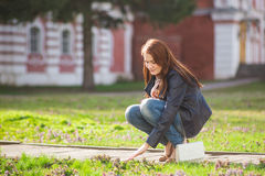 Brunette girl clothed in windbreaker hand touching young grass while walking on the  at springtime Stock Photo