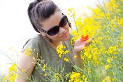 Brunette girl with a corn poppy in her hand Stock Photo