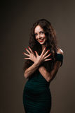 Brunette girl  with curly long hair shows Royalty Free Stock Images