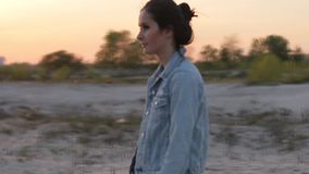 Brunette girl in the denim jacket is on wasteland stock footage