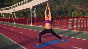 Woman practicing yoga standing on the bridge. Brunette girl doing yoga asana female with curly hair trains outdoors stock video