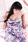Brunette girl in dress lying on sheet with hearts Stock Photo