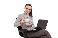 Brunette girl drinking coffe, sitting in the chair with laptop Stock Photos