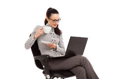 Brunette girl drinking coffe, sitting in the chair with laptop Royalty Free Stock Photo