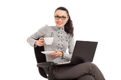 Brunette girl drinking coffe, sitting in the chair with laptop Stock Photo