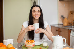 Brunette girl drinking tea in the moring in the kitchen Royalty Free Stock Photos