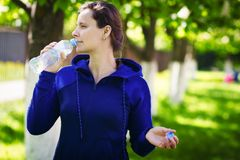 Brunette girl drinks drinking water from bottle in green summer park. Healthy lifestyle. Drinking clean water concept. stock photography